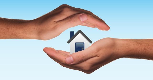 Lidské dlaně zastřešující piktogram domu